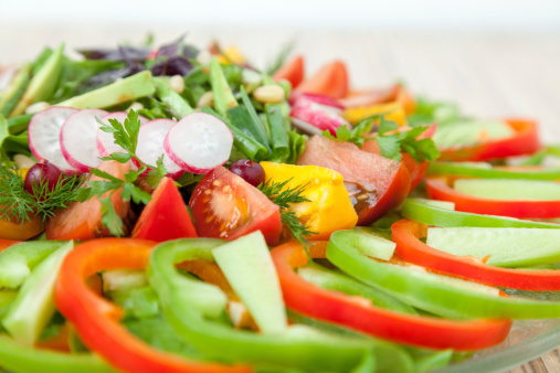 Vegetarian salad: fresh raw chopped vegetables on plate.